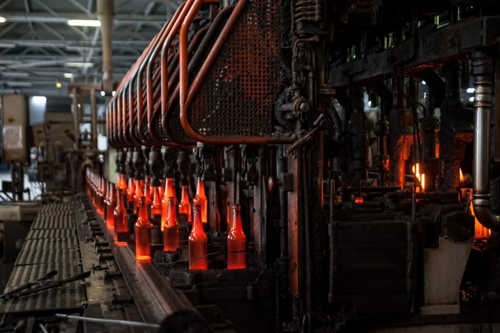 Automated line for the production of glass containers. The hot bottles are put on a moving conveyor