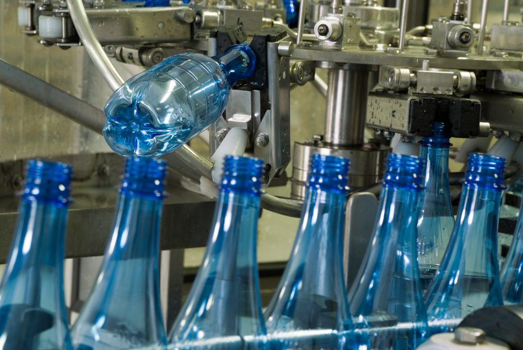 Plastic water bottles on conveyor or water bottling machine industry